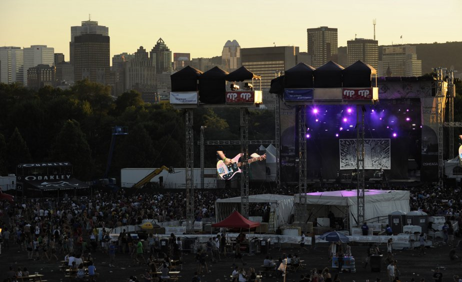 La foule sur le site au soleil couchant face au centre ville de Montréal. | 30 juillet 2011