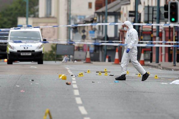 Les experts de la police examinent la scène... (Photo Paul Ellis, AFP)