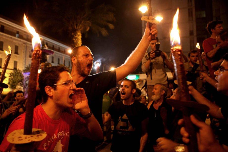 Des Israéliens chantent des slogans en brandissant des... (Photo Gali Ribbon, AFP)