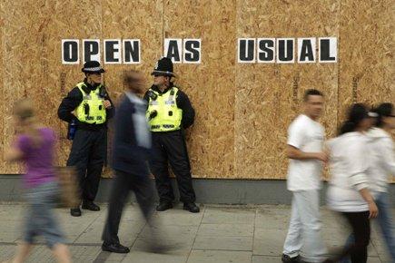 Des policiers en patrouille devant un commerce barricadé... (Photo: Reuters)