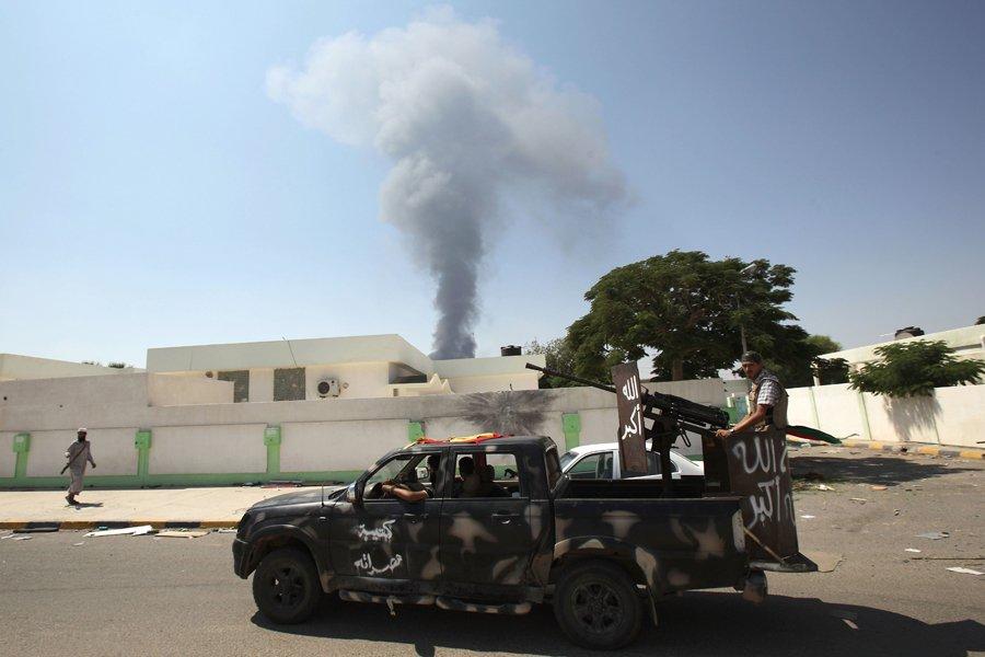 Des rebelles libyens circulent à proximité de l'ancien... (Photo: AFP)