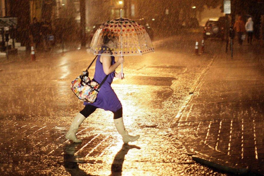 Une jeune femme rentre sous la pluie à... (Photo: Reuters)