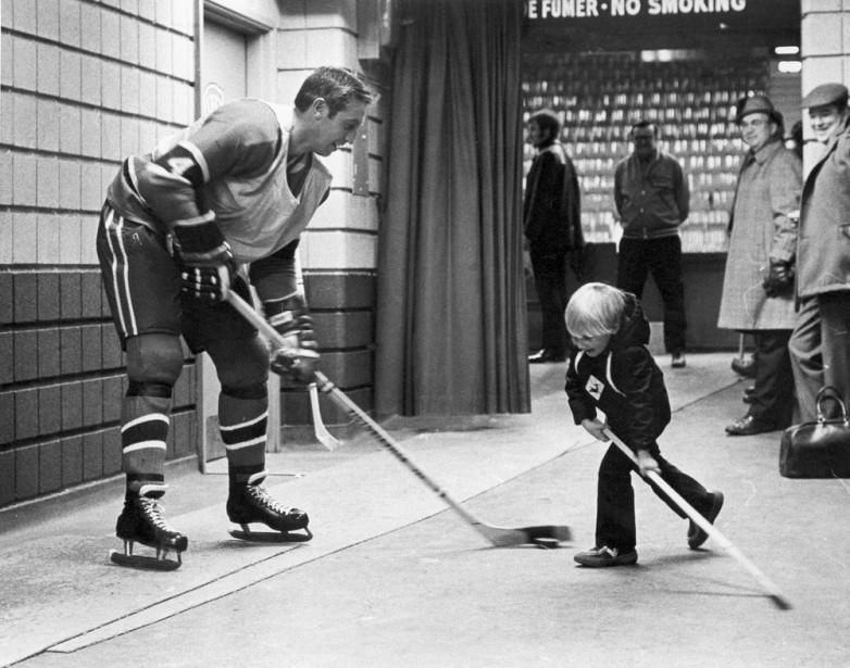 Jean Béliveau joue avec un jeune amateur chanceux. (Antoine Désilets, Archives La Presse)