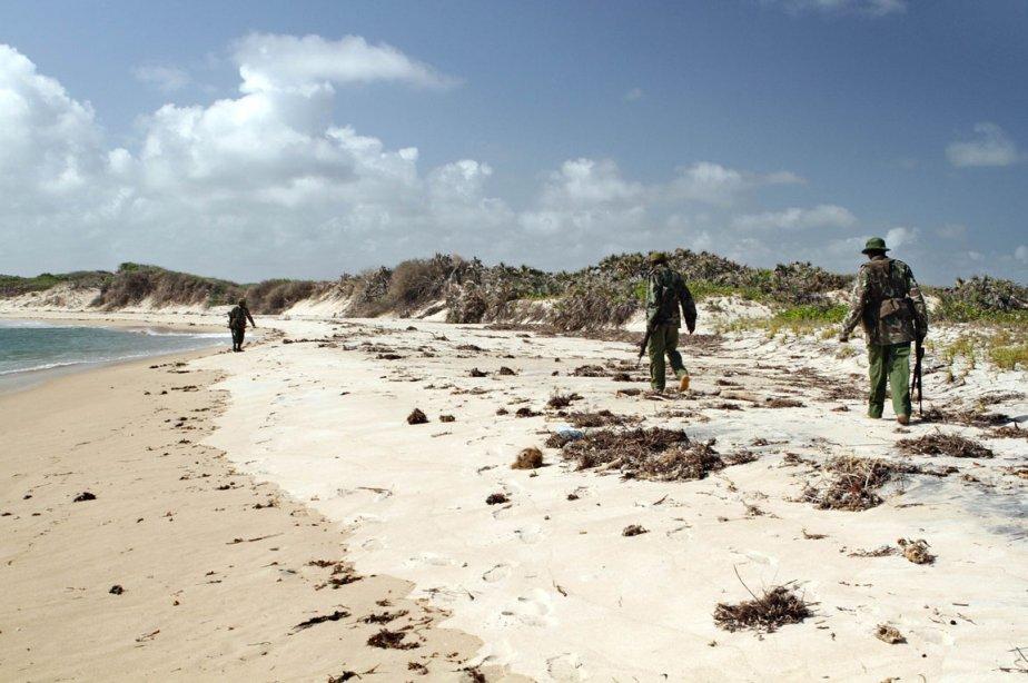 Des policiers parcourent la plage d'un village de... (Photo: William Davies, AFP)
