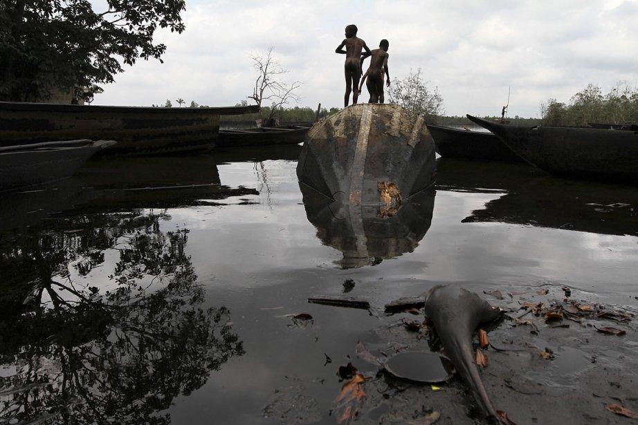 Deux enfants jouent sur un bateau abandonné près...