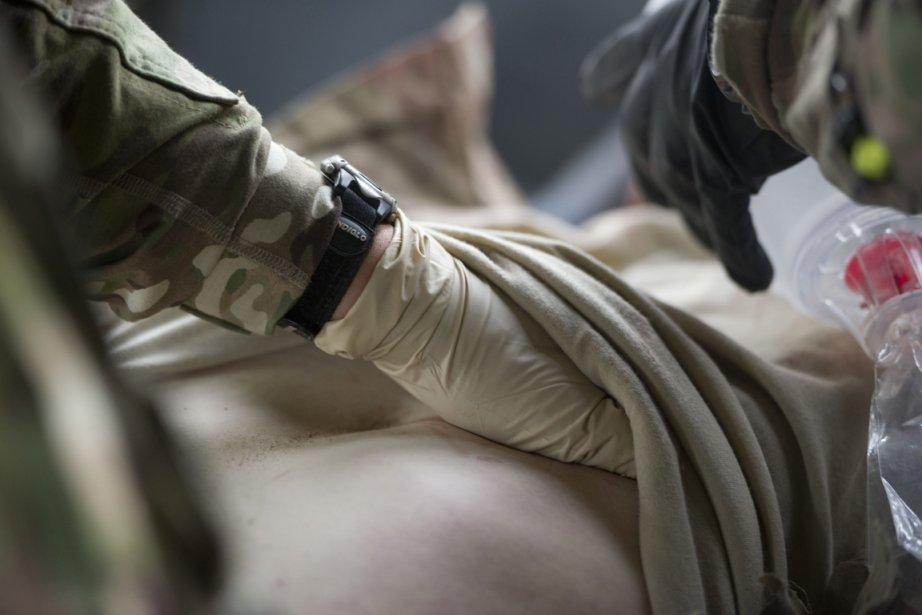 Un médecin apporte des soins à un soldat... (Photo: Johannes Eisele, AFP)