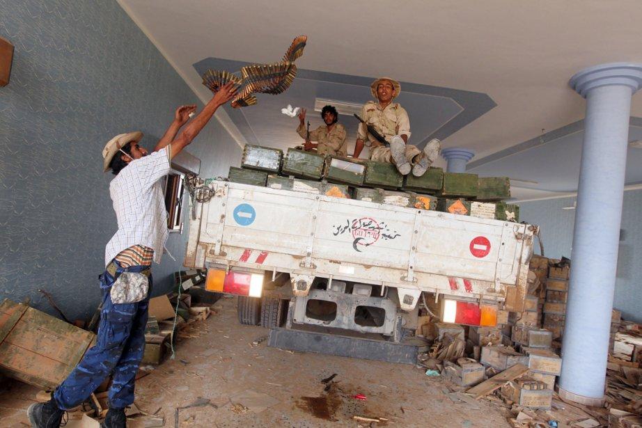 Des combattants du CNT chargent un camion avec... (Photo: Ahamd Al-Rubaye, AFP)