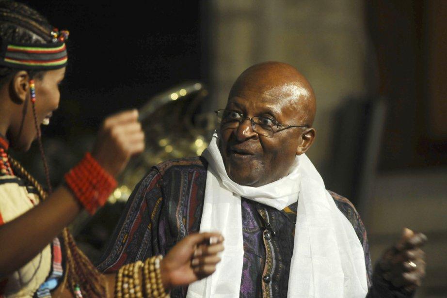Desmond Tutu danse avec une danseuse du Choeur... (Photo: Rodger Bosch, AFP)