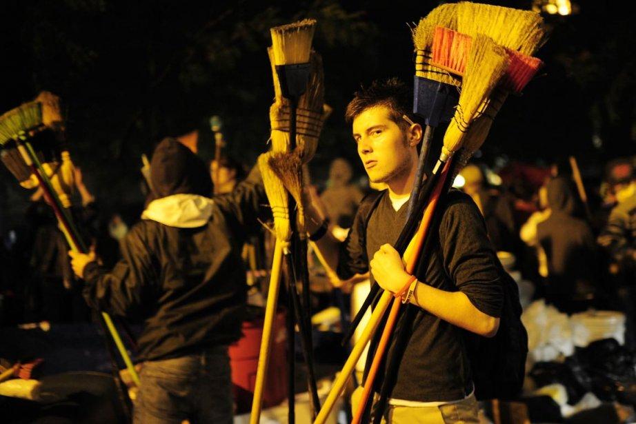 Des manifestants anti-Wall Street distribuent des balais à... (Photo: Emmanuel Dunand, AFP)