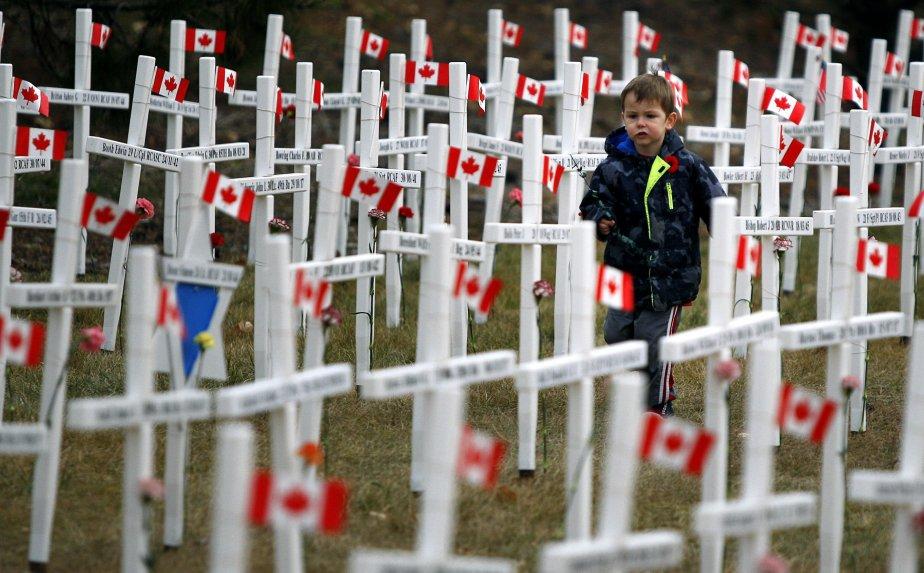 Un jeune garçon court à travers les quelque 3000 croix blanches représentant les soldats albertains tombés au combat, à l'occasion du jour du Souvenir, vendredi, à Calgary. | 11 novembre 2011