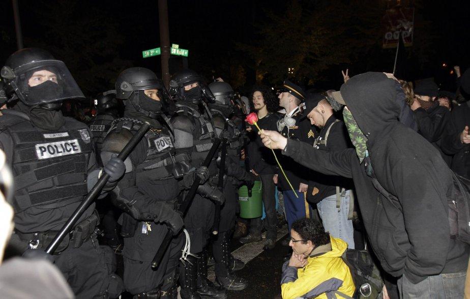 Un protestataire d'Occupy Portland offre une rose aux policiers venus forcer les occupants à quitter leur campement après avoir reçu un avis d'éviction de la Ville. Cette fois, ce sont les policiers qui ont reculé devant les milliers de manifestants rassemblés. | 13 novembre 2011