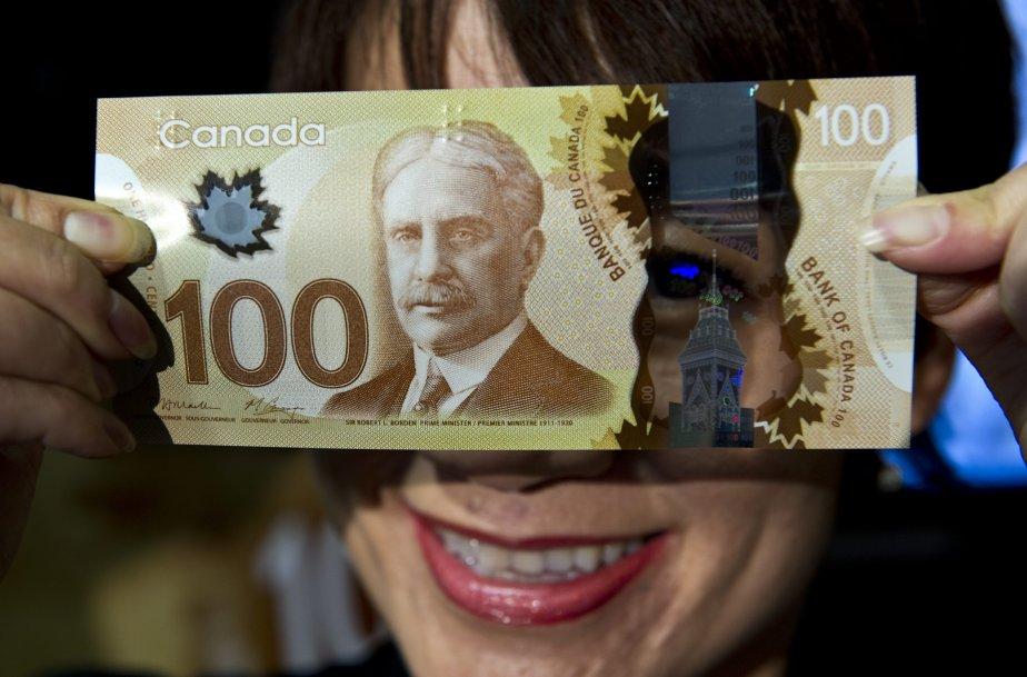 Phuong Anh Ho Huu, de la Banque du Canada, tient devant ses yeux un nouveau billet de 100 $, lancé le 14 novembre. La coupure de 100 $ est la première à être offerte dans une version en polymère présentant de nouvelles mesures de sécurité. | 14 novembre 2011