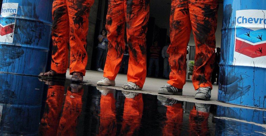 Des membres de Greenpeace, vêtus en travailleurs du pétrole, ont déversé le 18 novembre de la peinture noire sur les portes des bureaux de Chevron à Rio de Janeiro, pour protester contre une fuite de pétrole sur une installation de l'entreprise américaine au large du Brésil. | 18 novembre 2011