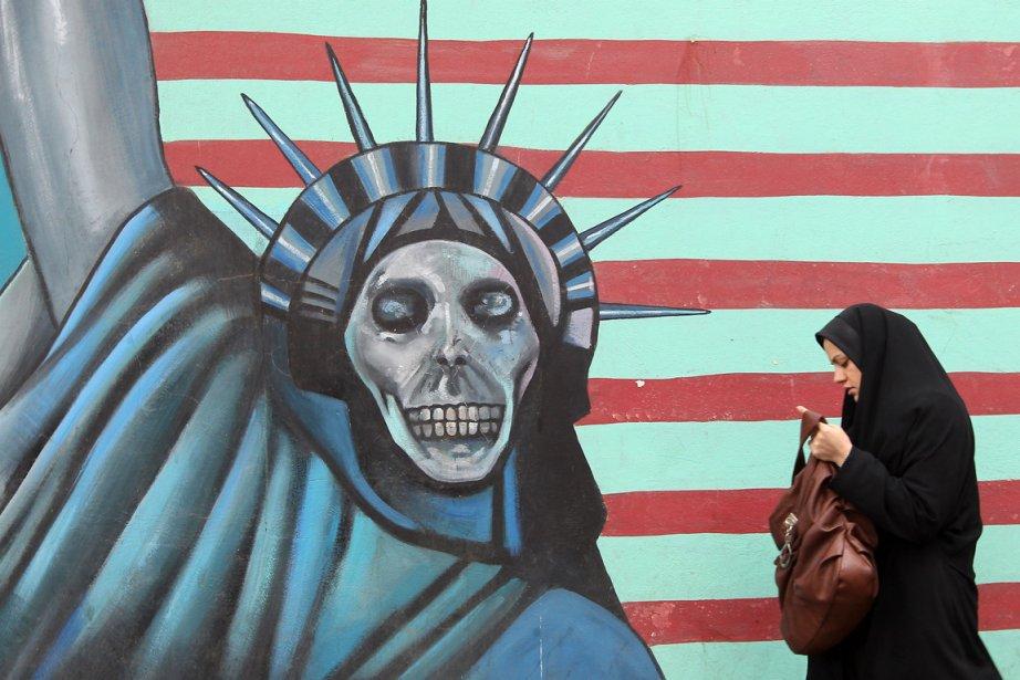Une Iranienne marche devant une murale dessinée sur... (Photo: ATTA KENARE, AFP)