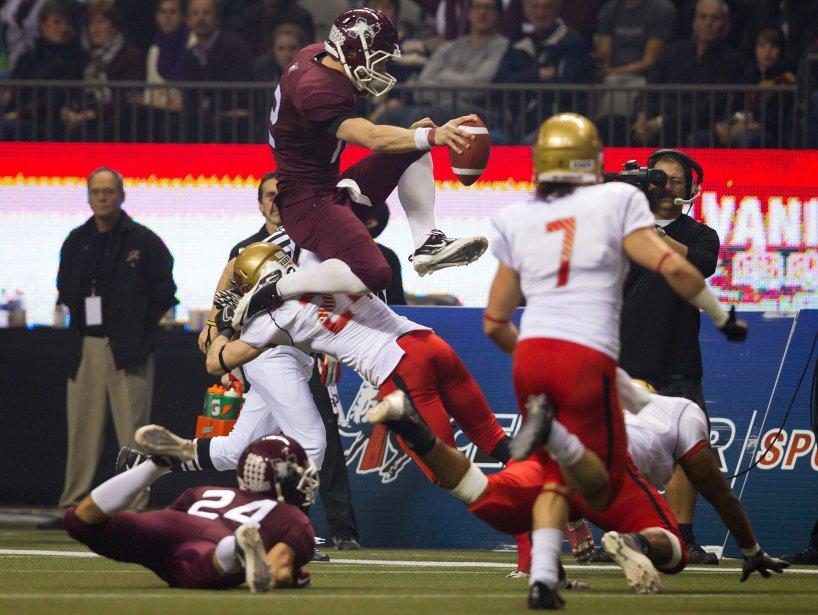 Le quart-arrière Kyle Quinlan des Marauders de l'Université McMaster saute par-dessus Dominic Noël, du Rouge et Or, alors qu'il tente d'obtenir un premier essai pendant la première demie de la Coupe Vanier, le vendredi 25 novembre, à Vancouver. L'équipe de l'Université Laval s'est finalement inclinée 41-38 devant McMaster. | 26 novembre 2011