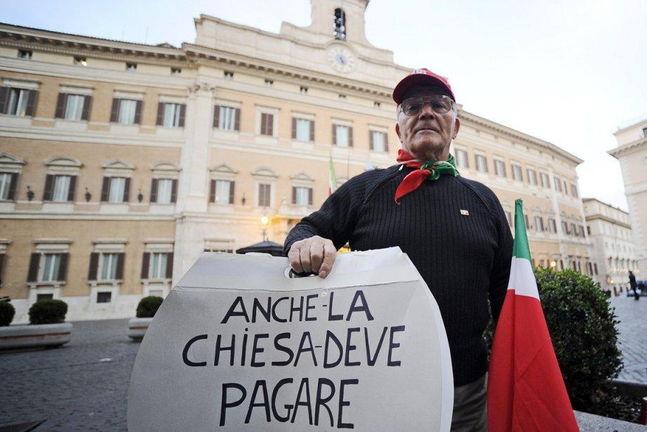 Un manifestant tient une pancarte où l'on peut... (Photo: Filippo Monteforte, AFP)