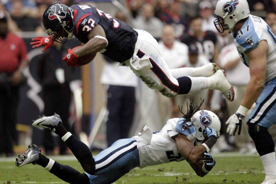 Derrick Ward plonge au-dessus de Robert Johnson durant... (Photo Brett Coomer, Houston Chronicle/AP)