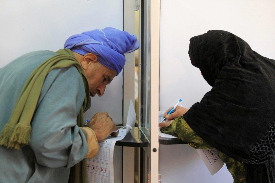 Des électeurs font leur choix à l'intérieur d'un... (Photo: Khaled Desouki, AFP)