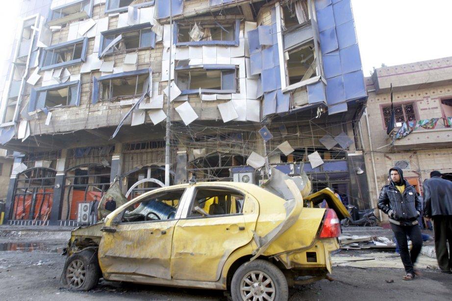 Des Irakiens marchent à proximité d'un véhicule utilisé... (Photo: Ali Al-Saadi, AFP)