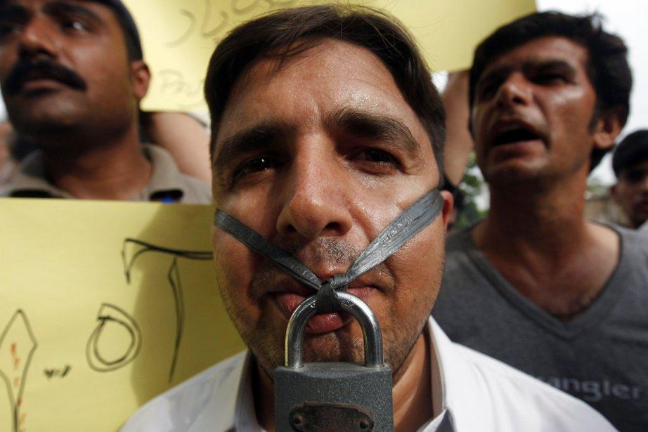 Un journaliste, la bouche cadenassée, participe à une... (Photo: Athar Hussain, Reuters)