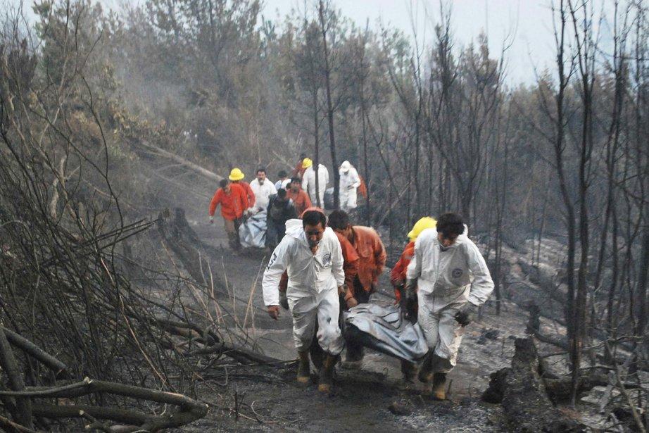 Des secouristes évacuent le corps d'un pompier ayant... (Photo: Hector Andrade, Reuters)