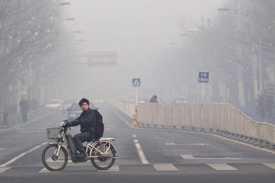 Un Pékinois conduit sa mobilette dans une rue... (Photo: Andy Wong, AP)