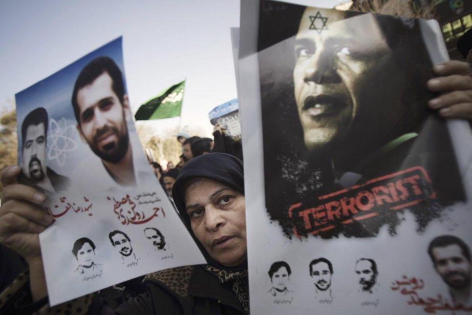 Une femme exhibe deux affiches, l'une à l'effigie... (Photo: Morteza Nikoubazl, Reuters)