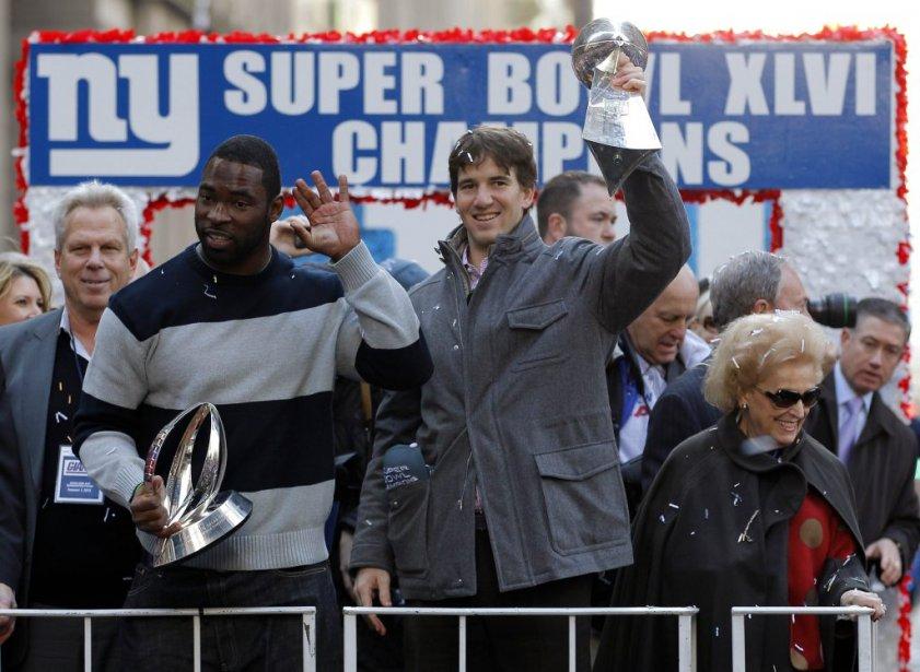 Justin Tuck et Eli Manning saluent la foule. | 7 février 2012