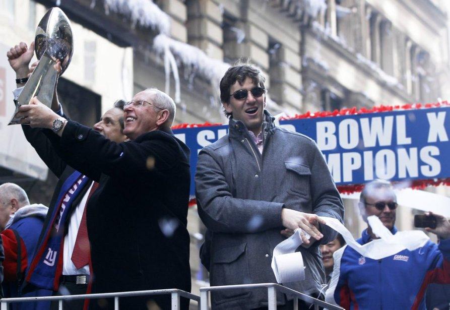 L'entraîneur-chef des Giants Tom Coughlin brandit le trophée Vince Lombardi, aux côtés du quart Eli Manning. | 7 février 2012