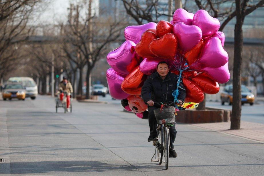 Un vendeur itinérant, au guidon de son vélo, transporte une cargaison de ballons en forme de coeur dans une rue de Pékin. | 14 février 2012