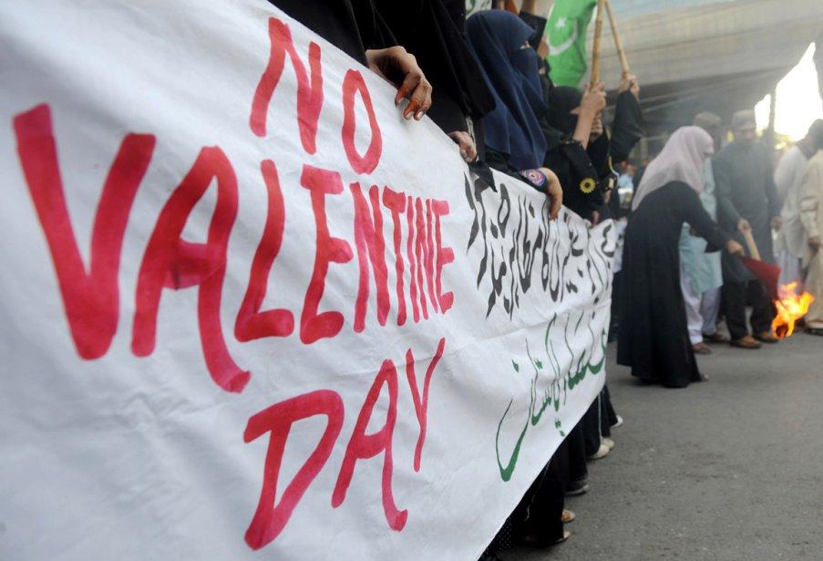 Des femmes du parti islamique Jamiat Ulema-e-Islam portent une bannière où l'on peut lire «Non à la Saint-Valentin», lors d'une manifestation dénonçant la fête de Cupidon, alors qu'une protestataire brûle une carte de la Saint-Valentin en guise de protestation. | 14 février 2012