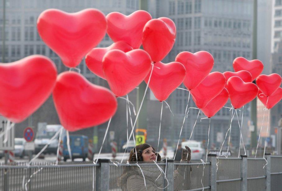 Une femme attache des ballons en forme de coeur à... | 2012-02-14 00:00:00.000