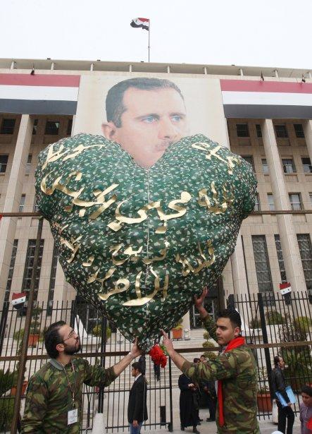 Des partisans du président syrien Bachar Al-Assad, vêtus en treillis militaires, tiennent un ballon géant en forme de coeur, d'un vert camouflage plutôt que d'un rouge valentin, au dessous d'un portrait du dirigeant contesté, lors d'une manifestation de soutien à M. Assad dans les rues de Damas. Pendant ce temps la «capitale de la rébellion» Homs, essuyait ses pires bombardements depuis les cinq derniers jours. | 14 février 2012