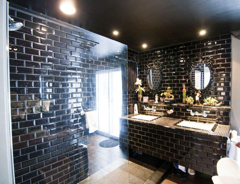 Cette pièce couverte de céramique métro noire jouxte la chambre principale, dont on voit la porte-fenêtre reflétée par la paroi de la douche. | 24 février 2012