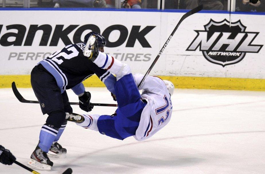 Erik Cole tombe devant Jason Garrison. | 26 février 2012
