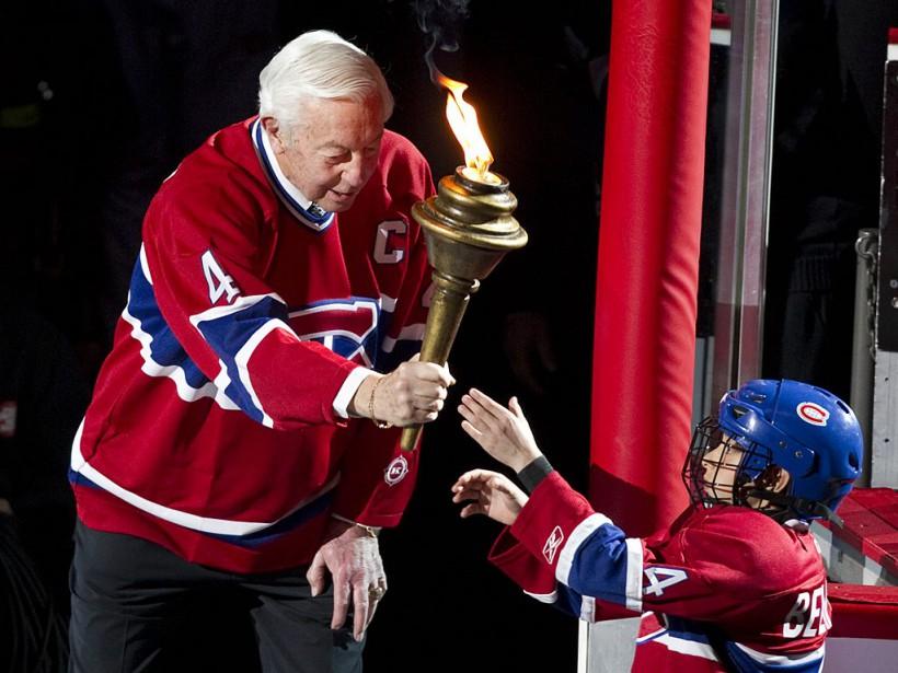 Jean Béliveau passe le flambeau à un jeune enfant avant un match des séries éliminatoires contre les Bruins de Boston, le 18 avril 2011, au Centre Bell. (André Pichette, La Presse)