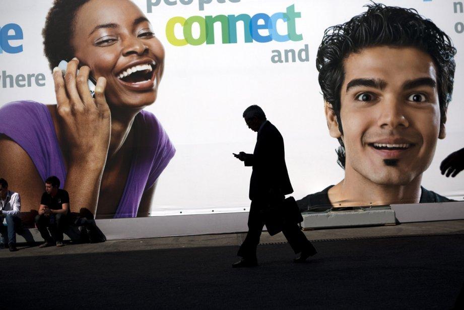 Un homme utilise son cellulaire en passant devant... (Photo: AP)