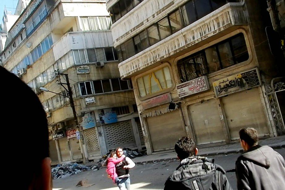 Un homme court avec une petite dans les... (Image: AFP)