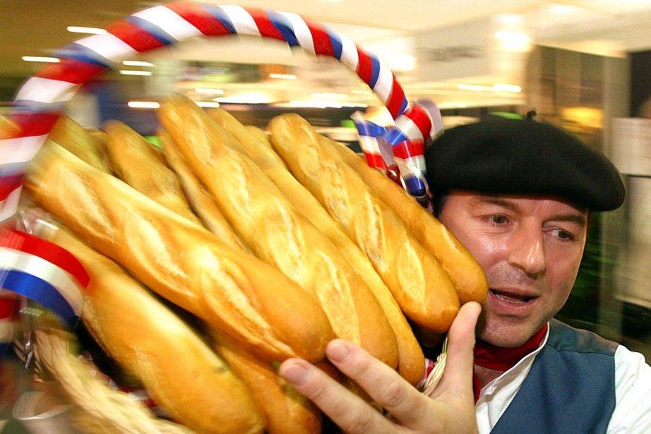 Un boulanger français transporte un panier rempli de... (Photo AFP)