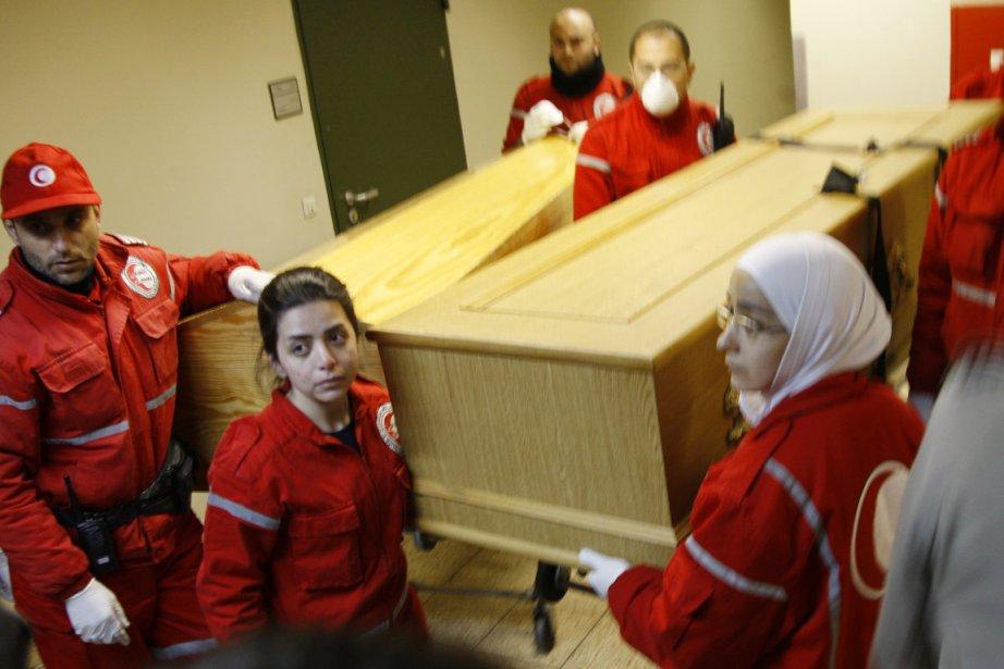 Des membres du Croissant-Rouge syrien portent les cerceuils... (Photo: Khaled al-Hariri, Reuters)