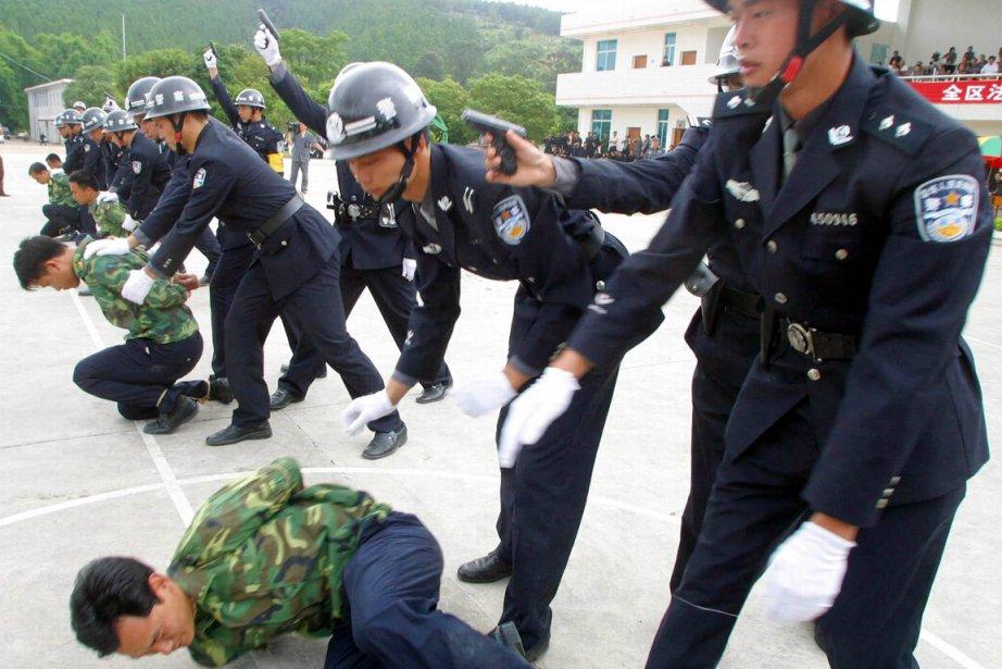 Des policiers pratiquent, sur des collègues, l'exécution de... (Photo: Archives AP)