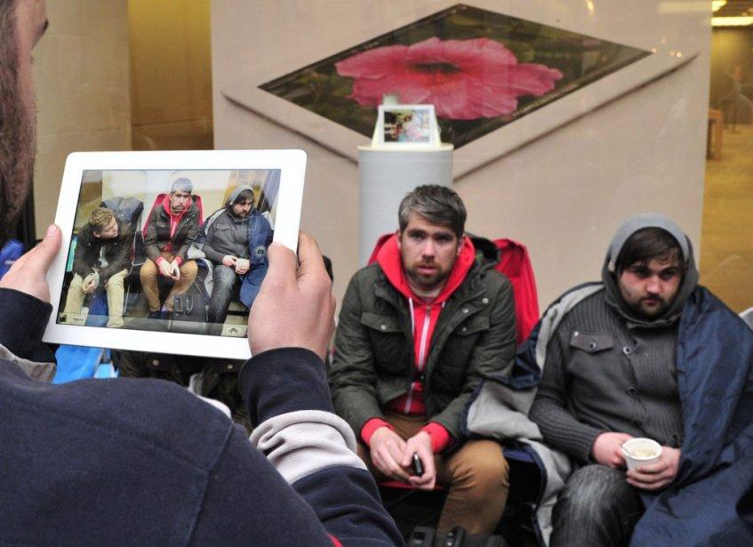 Un homme utilise son nouvel iPad pour prendre en photo des gens qui ont attendu 48 heures en ligne devant le magasin d'Apple à Londres. (Photo: Reuters)
