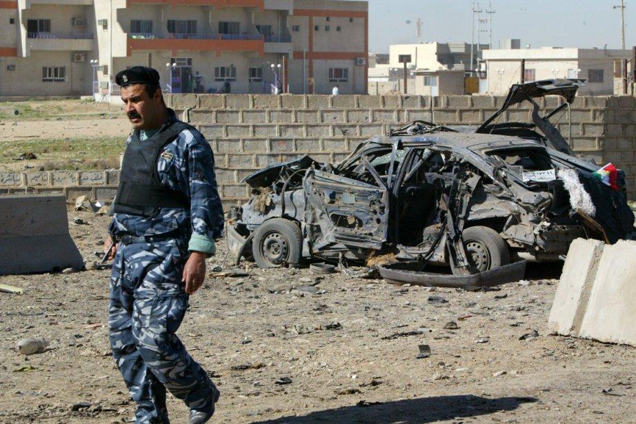 Un policier irakien marche à proximité d'une voiture... (Photo: Marwan Ibrahim, AFP)