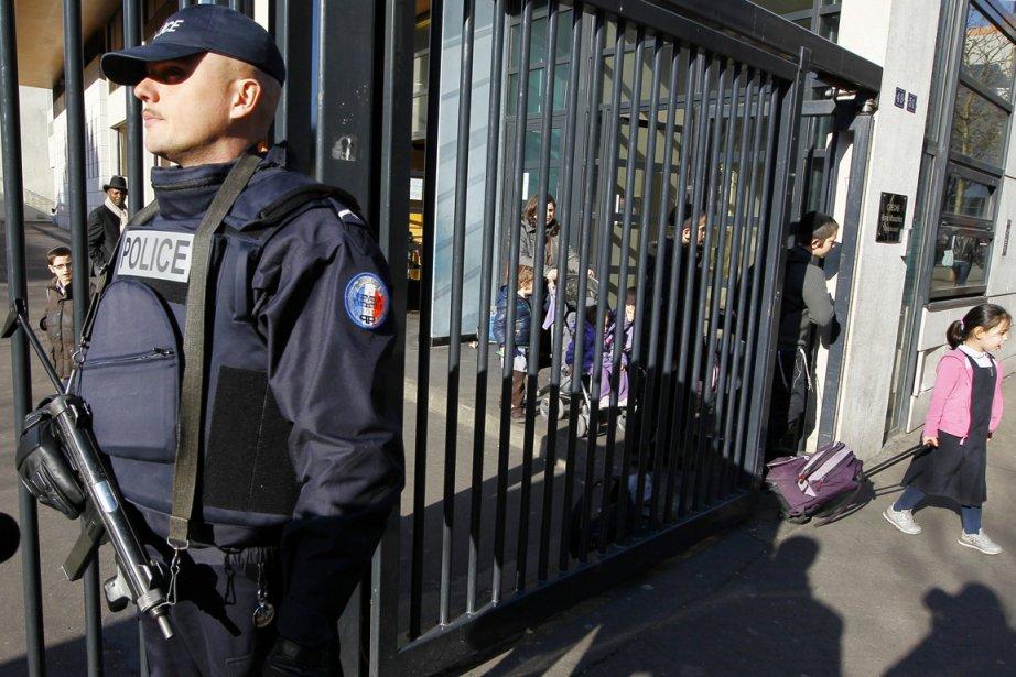 Un policier monte la garde devant une école... (Photo: François Mori, AP)