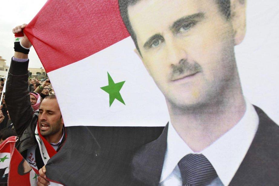 Un partisan du président syrien Bachar al-Assad brandit... (Photo: Muhammad Hamed, Reuters)