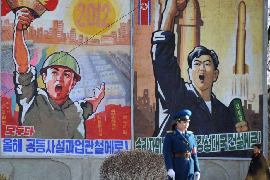 Une policière est photographiée devant des affiches propagandistes,... (Photo: AP/Kyodo News)