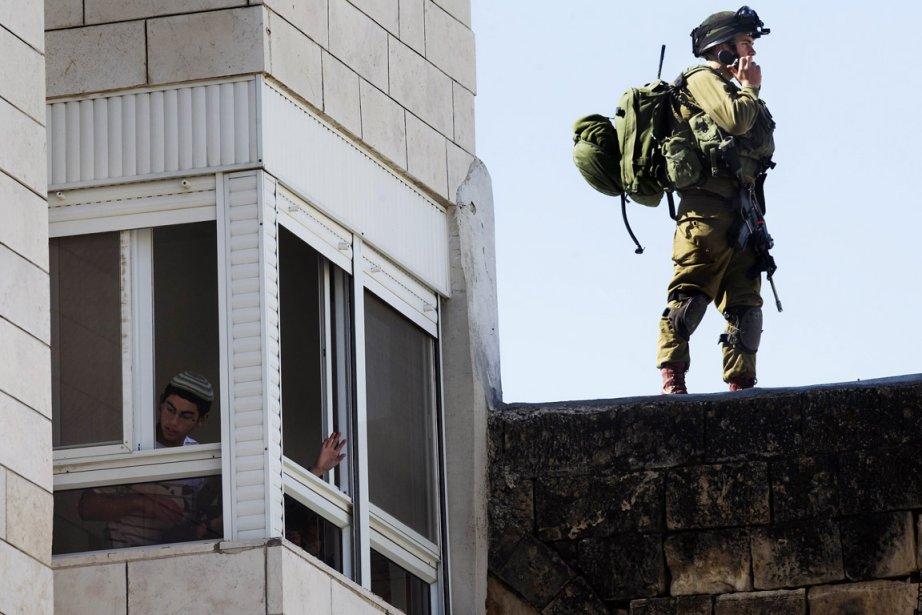 Un colon israélien regarde à travers la fenêtre... (Photo: Menahem Kahana, AFP)