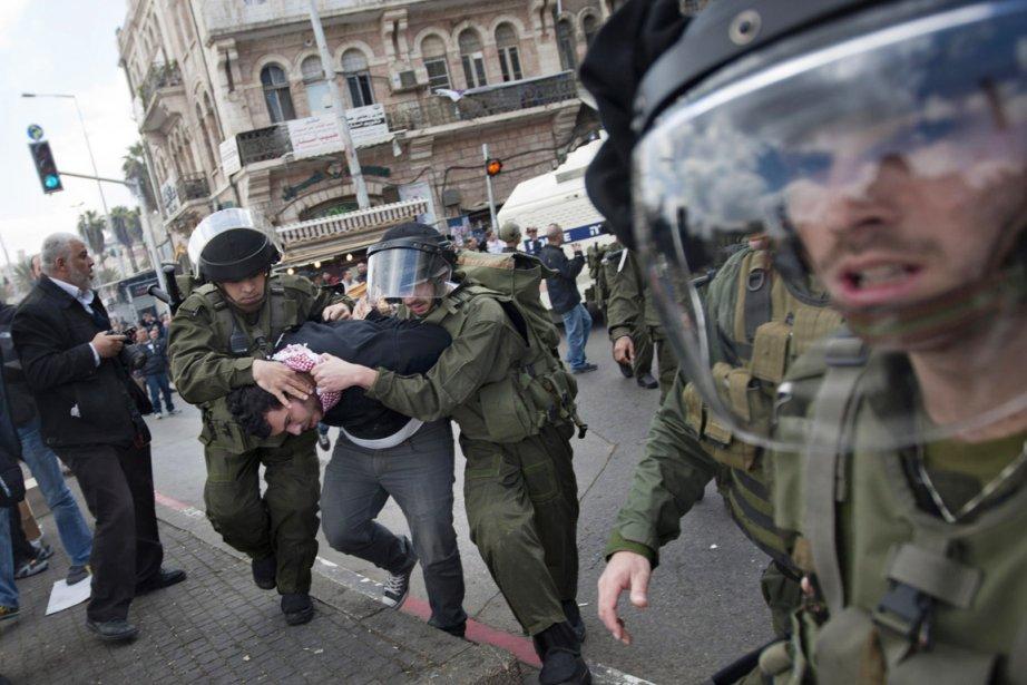 Les policiers israéliens procèdent à l'arrestation d'un Palestinien,... (Photo: Sebastian Scheiner, AP)