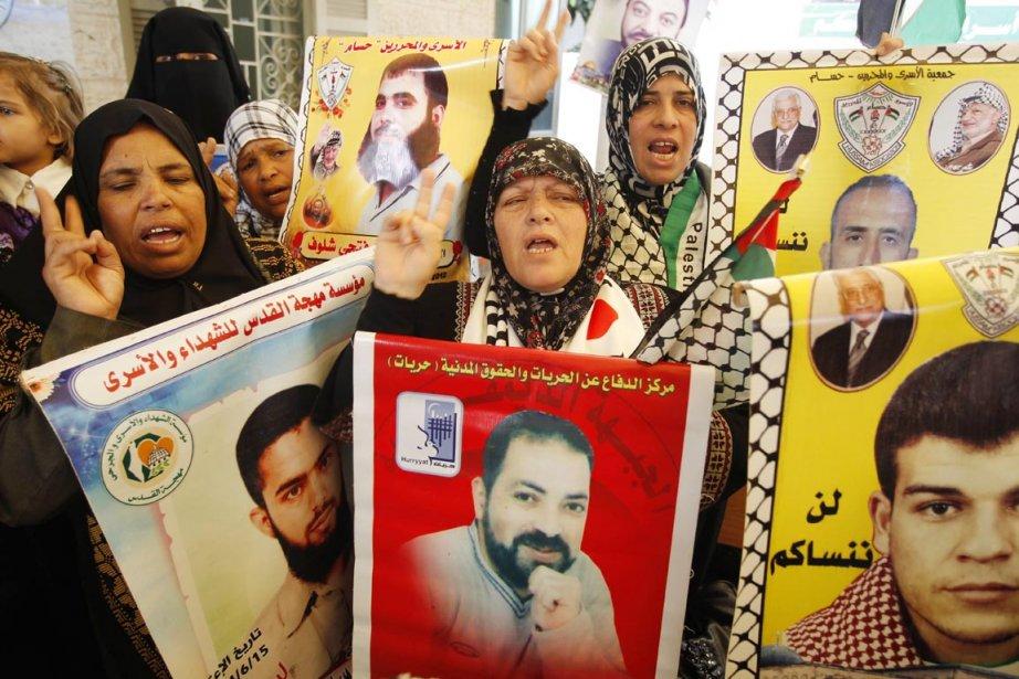 Des Palestiennes brandissent les portraits de leurs proches... (Photo: Mohammed Abed, AFP)