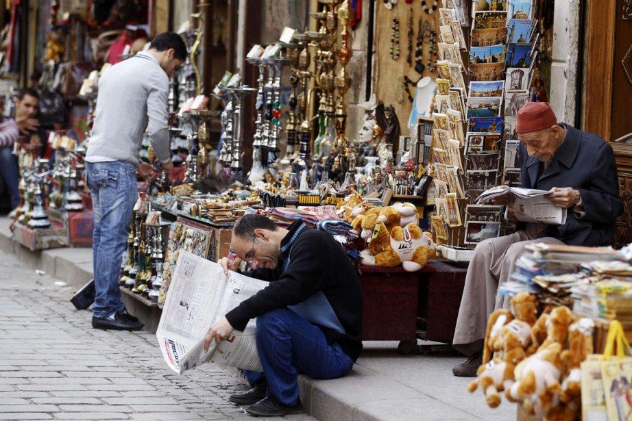 Des vendeurs lisent les journaux sur le trottoir... (Photo Peter Andrews, Reuters)